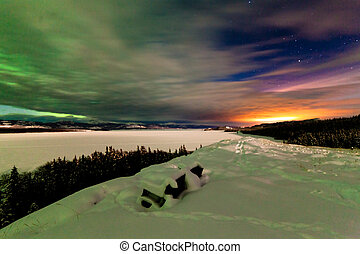 Northern Lights and city light pollution night sky -...