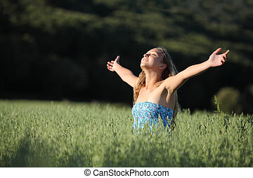 Beautiful teenager girl breathing happy in a green meadow -...