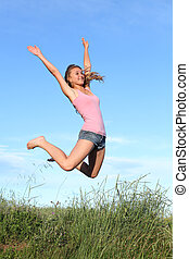 Blonde teenager girl jumping happy in the mountain with the...