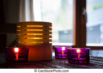tea candles in wood and glass standing on reed mat