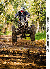 Quad rider jumping on a forest trail.