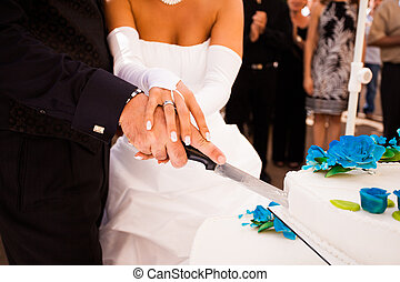 wedding cake - couple cutting white wedding cake with blue...
