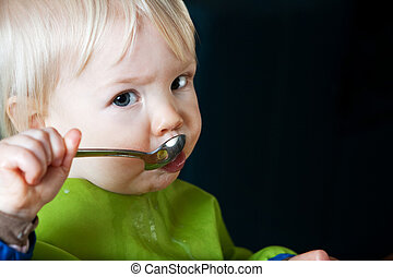 Child Eating with Spoon - Young toddler eating with a spoon...