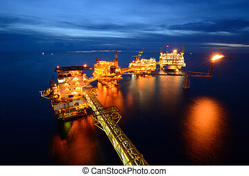 The large offshore oil rig at night with twilight background...