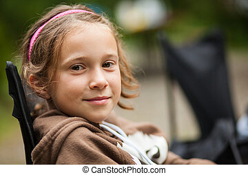 Girl smiling while sitting outdoor