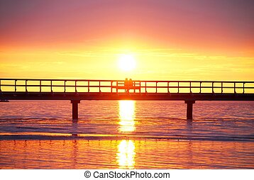 couple in the sunsetting - a couple sitting on a bridge...