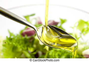 Pouring oil - Pouring olive oil in the salad over a spoon