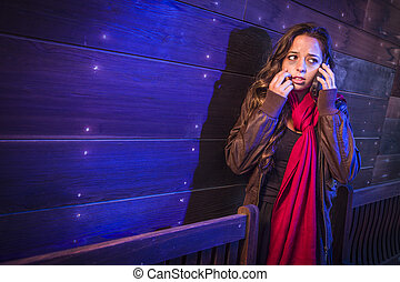 Frightened Young Woman in Dark Walkway Using Cell Phone