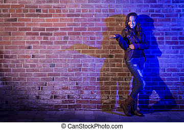 Mixed Race Woman Holding Her Hand Out Against Brick Wall