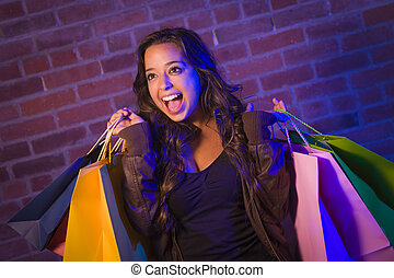 Mixed Race Young Woman Holding Shopping Bags Against Brick Wall