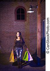 Mixed Race Young Woman Walking Carrying Shopping Bags at Night