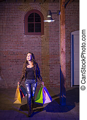 Mixed Race Young Woman Walking Carrying Shopping Bags at Night