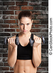 Woman Working Out - Woman working out with dumbbells at a...