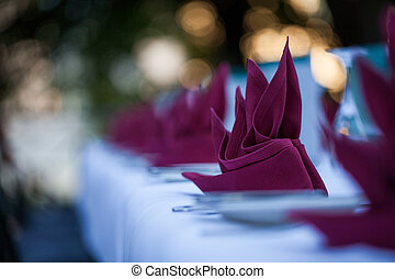 folded napkin - folded purple napkins on a table