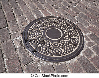 Manhole cover on old pink granite cobblestone street