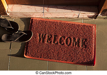 welcome doormat - a red welcome doormat next to a couple of...