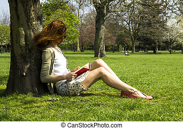 Young woman reading in park