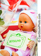 baby doll holding sign with New Zealand written on it
