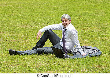Having my break in a park - A young businessman having a...