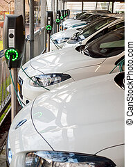 electric cars being recharged - row of plug-in electric...