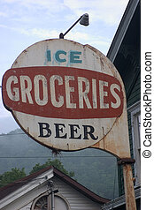 An old weathered and rusted sign sits outside an abandoned...