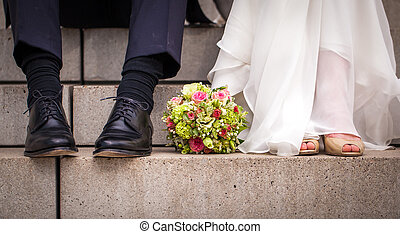 bride and groom - feet of a bridal couple sitting on steps...