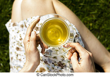 Close up on cup of tea in the hands of young woman
