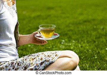 Young woman drinking tea in the park