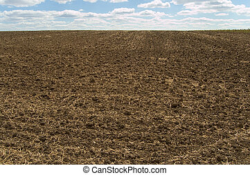 ploughing - black arable soil at autumn after harvest