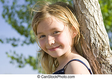 6 year old smiling girl leaning against tree