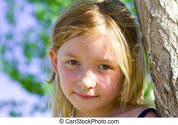 6 year old girl smiling leaning against a tree in the park
