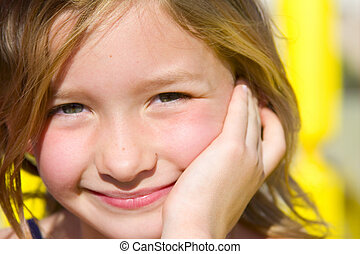 6 year old smiling girl in fron of yellow playground...