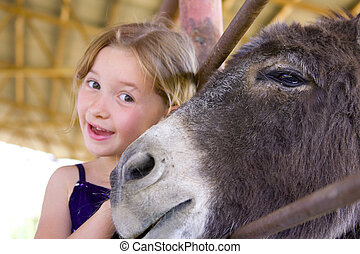 6 year old girl wearing a blue shirt smiling next to donkey...