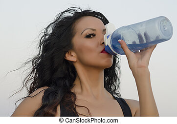 Woman drinking water from bottle - Woman quenching thirst...