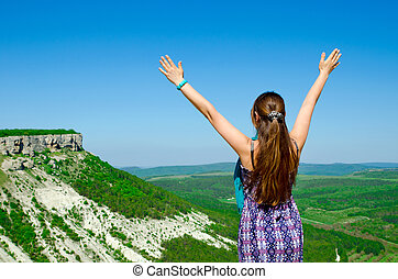 woman in mountain with hands up