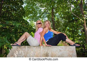Female friends sitting on a rock - Female friends sitting...