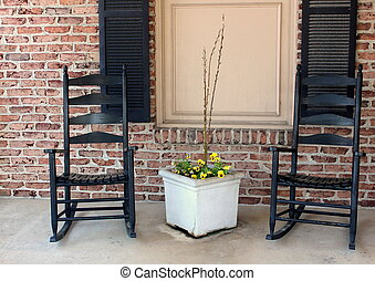 Two black rocking chairs on porch
