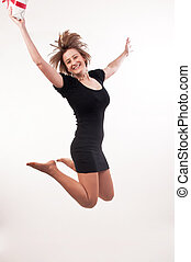 happy young woman jumping with gift box in her hand