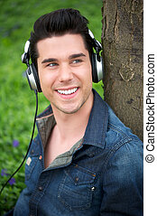 Handsome young man listening to music outdoors