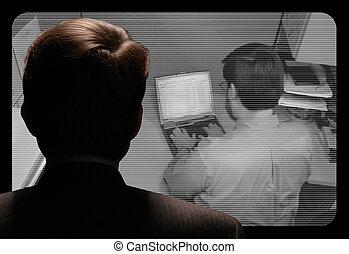 Man observing an employee work via video camera - Man...