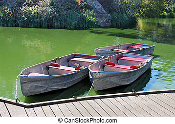 Three Boats on Lake - Three boats docked on a lake on a...