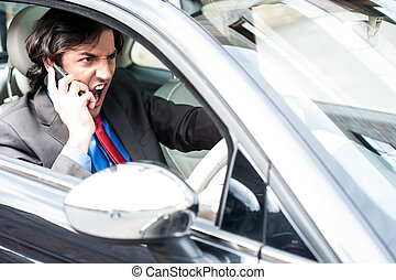 Angry businessman shouting while driving - Angry young male...