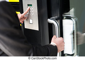 Man entering security code to unlock the door - Businessman...