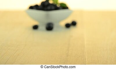 Blueberries on white ceramic bowl on wooden table.
