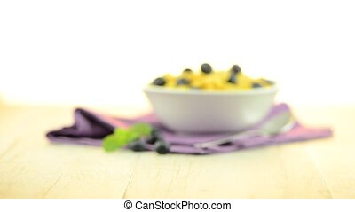 Cereal and blueberries on white ceramic bowl on wooden table...
