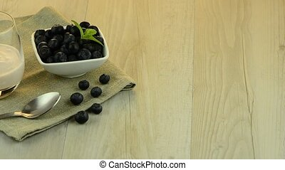 Yogurt and blueberries set on a wooden table