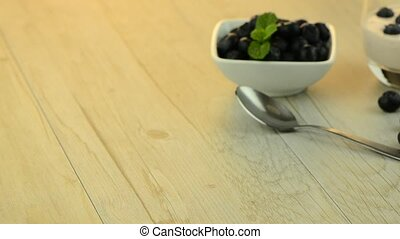 Yogurt and blueberries set on a wooden table.