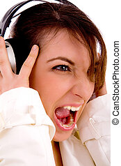 side pose of screaming woman listening to music with white...