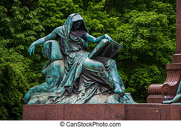 statue - female statue reading a book while sitting on a...