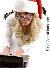 high angle view of woman in christmas hat working on laptop...